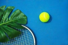 Sommertenniskonzept mit grünem monstera Blatt und Ball, Schläger auf hartem Tennisplatz stockbild