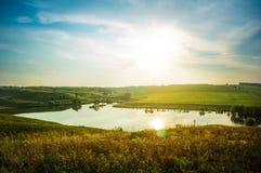 Sommerwiese und -teich am hellen sonnigen Tag Sonnige Landschaft mit Lizenzfreie Stockfotos