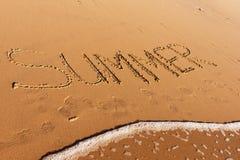 Sommerwort geschrieben in den Strand Stockbild