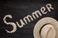 Sommerzeichen mit Hut auf hölzernem Hintergrund Stockfotografie