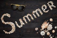 Sommerzeichen mit Sonnenbrille und Muscheln auf hölzernem Hintergrund Lizenzfreie Stockbilder