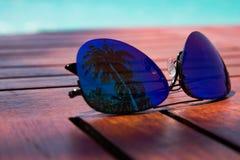 sommerzeit Artgläser mit Palmenreflexion, die auf einem Holztisch auf der Küste des karibischen Meeres fand lizenzfreies stockfoto