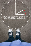 Sommerzeit, German Daylight Saving Time on asphalt with two shoe Royalty Free Stock Images