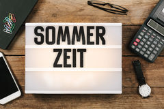 Sommerzeit, German Daylight Saving Time in vintage style light b. Ox on office desktop, high angle birds eye view royalty free stock image