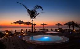 Sommerzeit: schöne Dämmerung am Poolbereich mit Palme und Sonnenschirmen, Stockfotografie