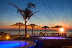 Sommerzeit: schöne Dämmerung am Poolbereich mit Palme und Sonnenschirmen, Lizenzfreies Stockbild