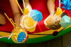 Sommerzitrusfruchtcocktails mit Regenschirmen in den Händen von Mädchen Re lizenzfreie stockfotografie