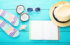 Sommerzubehör und -notizbuch mit Kopienraum auf blauem hölzernem Hintergrund Beschneidungspfad eingeschlossen Stockbild