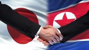 Sommet international d'amitié de poignée de main du Japon et de la Corée du Nord, fond de drapeau banque de vidéos