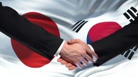 Sommet international d'amitié de poignée de main du Japon et de la Corée du Sud, fond de drapeau banque de vidéos
