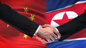 Sommet international d'amitié de poignée de main de la Chine et de la Corée du Nord, fond de drapeau banque de vidéos