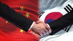 Sommet international d'amitié de poignée de main de la Chine et de la Corée du Sud, fond de drapeau banque de vidéos