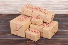 Sommige die document de giftvakjes van pakkettenkerstmis met document kraftpapier worden en met rode witte bakkersstreng worden g Royalty-vrije Stock Foto's
