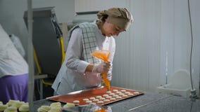 Sommige gebakjechef-koks aan het werk in een suikergoed winkelen Één van de vrouwen betrokken bij de verwezenlijking van deegware stock footage
