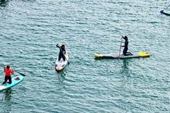 Sommige jongens en meisjes paddelen op een raad op de oppervlakte van het overzees Mening van hierboven stock fotografie