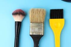 Sommige kosmetische borstels en één borstel voor het schilderen van muren stock afbeelding