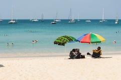 Sommige mensen ontspannen op het strand Stock Foto's