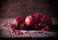 Sommige rode granaatappels op oude houten lijst Royalty-vrije Stock Afbeeldingen