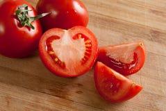 Sommige rode tomaten op scherpe raad Royalty-vrije Stock Afbeelding