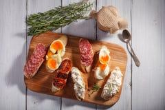 Sommige sandwiches op witte houten achtergrond Stock Afbeeldingen