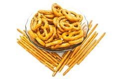 Sommige smakelijke gezouten pretzels en breadsticks op wit Stock Afbeelding