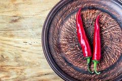 Sommige Spaanse peperpeper op donkere plaat, verse rode rijpe hete Spaanse pepers op oude houten raadsachtergrond met exemplaarru Royalty-vrije Stock Foto's