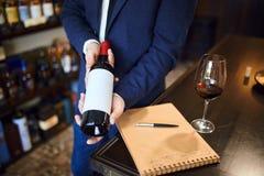 Sommilier som väljer flaskan av vin arkivbilder