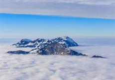 Sommità delle alpi svizzere che aumentano da un mare di nebbia nell'inverno Immagine Stock