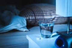 Somnífero en nightstand al lado de un vidrio de agua Imagen de archivo