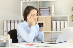 Somnolent executive drinking coffee at office royalty free stock photography