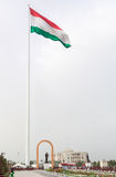 Somoni statue in front of the flag of Tajikistan. Dushanbe Royalty Free Stock Photo