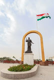 Somoni statue in front of the flag of Tajikistan. Dushanbe Royalty Free Stock Images
