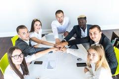 Somos el gran equipo Grupo de hombres de negocios felices que llevan a cabo las manos juntas mientras que se sienta alrededor del foto de archivo libre de regalías