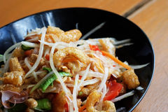 Somtam (Papaya Salad) with pork crackling. Photo of Somtam (Papaya Salad) with pork crackling royalty free stock photography