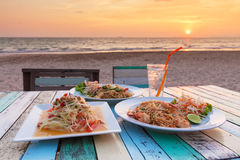 Somtum ,Pad Thai. Stir fry noodles with shrimp - and the view of  sunset at Banana Garden Home on Klong Dao Beach - Lanta Island - Krabi - Thailand Stock Photos