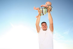 Son. Young father holding baby at the sunny beach Royalty Free Stock Photos