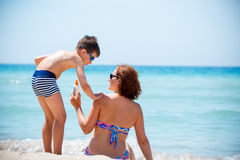 Son applying sunblock cream on his mother shoulder Royalty Free Stock Photography