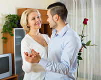 Son asking mother to dance at home. Russian son asking senior mother to dance at home royalty free stock image