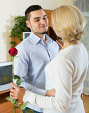 Son asking mother to dance at home. Son asking senior mother to dance at home royalty free stock photography