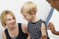 Son Being Injected By A Female Doctor Stock Image