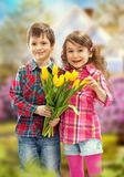 Son with bouquet preparing surprise for mother Stock Images