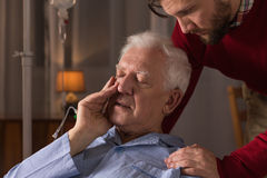 Son caring about dying father. Photo of son caring about dying father Stock Photography