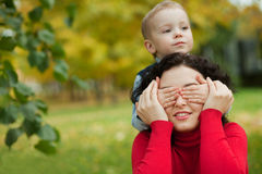 Son closes his eyes Mom. Son mother closes her eyes in the park in autumn Stock Photography