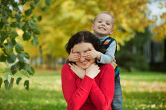 Son closes his eyes Mom. Son mother closes her eyes in the park in autumn Stock Photos