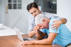 Son comforting tensed father sitting at desk. With laptop Royalty Free Stock Image