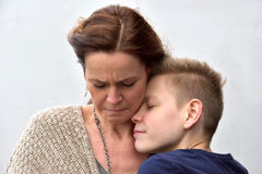 Son comforts mother. Teenager son comforts his sad mother stock image