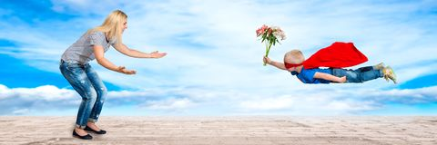 The son in the costume of a superhero flies with a bouquet of flowers to her beloved mother. royalty free stock image