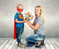The son in the costume of a superhero gives his mother a bouquet of flowers. stock photo