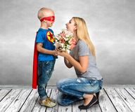 The son in the costume of a superhero gives his mother a bouquet of flowers. Surprise for mom Royalty Free Stock Images