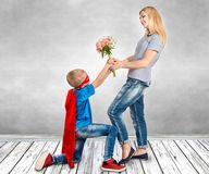 The son in the costume of a superhero gives his mother a bouquet of flowers. Surprise for mom Stock Image